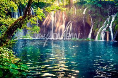 Fotomural La última luz del sol ilumina la cascada de agua pura en el Parque Nacional de Plitvice